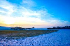 Sikt av en solnedgång över winterly ett landskap arkivbild