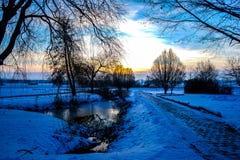 Sikt av en solnedgång över winterly ett landskap arkivfoto