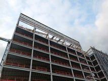 Sikt av en stor byggande utveckling under konstruktion med stålramen och balkar som stöttar metallgolven med b arkivfoto