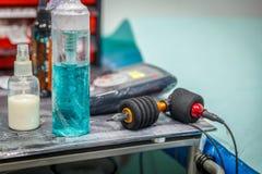 Sikt av en tatueringmaskin, tillsammans med flaskor och andra instrumen Arkivbilder