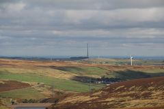 Sikt av en vindlantgård med turbiner på penninesna, UK Royaltyfri Bild