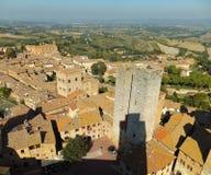 Sikt av ett avsnitt av San Gimignano på bakgrunden av det Tuscan landskapet som tas från Torre Grossa som gjuter en skugga fotografering för bildbyråer