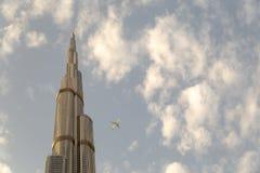 Sikt av ett Boing flygplan som nästan flyger Burj Khalifa i Dubai arkivbild