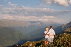 Sikt av ett par som håller ögonen på solnedgången på en äng och berget royaltyfri fotografi