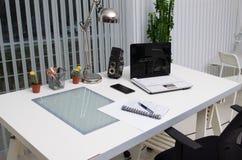 Sikt av ett vitt funktionsdugligt skrivbord på kontoret Royaltyfria Bilder
