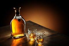 Sikt av exponeringsglas av bourbon och en flaska åt sidan Arkivbild