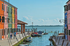Sikt av färgrika byggnader, folk och fartyg framme av en kanal på Burano Royaltyfria Foton