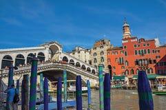 Sikt av färgrika byggnader, gondoler och den Rialto bron med folk på Venedig Royaltyfri Fotografi