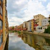 Sikt av färgrika hus och deras reflexion i en kanal i Girona, Spanien royaltyfri foto
