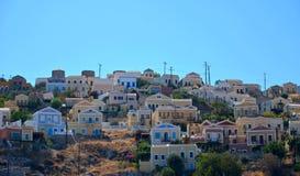 Sikt av färgrika hus på en kulle i den Simi ön mellan Grekland och Turkiet Royaltyfri Bild
