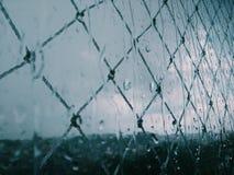 Sikt av fönstret med regndroppar på blå dag royaltyfri foto