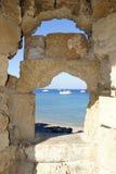 Sikt av fjärden till och med en kryphål i väggen på ön av Rhodes i Grekland Royaltyfri Foto