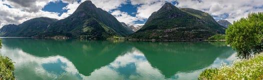 Sikt av fjordarna, reflekterad i det lugna vattnet från andra sidan av floden royaltyfri bild
