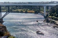 Sikt av floden Douro och broarna D Maria Pia och infanten, bankerna och fartygen som seglar på floden royaltyfria bilder