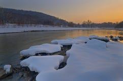 Sikt av floden efter solnedgång i vinter ovanför ljus lugna stad clouds den mörka önskande solnedgången för solljus för scatteren Royaltyfria Foton