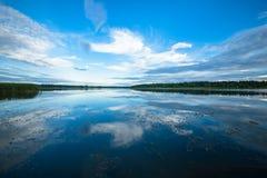 Sikt av floden från kusten med en härlig himmel och moln Royaltyfri Bild