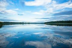 Sikt av floden från kusten med en härlig himmel och moln Royaltyfria Bilder