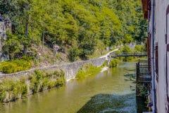 Sikt av floden Nive, som den passerar till och med byhelgonet Jean Pied de Port aquitaine france royaltyfria foton
