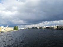 Sikt av floden och byggnaderna mot den dystra himlen och molnen i Petersburg arkivfoto