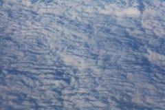 Sikt av flygplanfönstret på horisonten och molnen Royaltyfri Bild