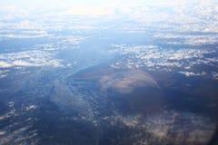 Sikt av flygplanfönstret på horisonten och molnen Arkivbilder