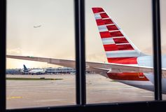 Sikt av flygplanflygkroppsvansen till och med fönster på flygplatsen arkivbild