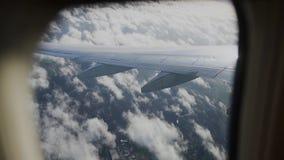 sikt av flygplanvingen till och med plant fönster ovanför att flyga för oklarheter arkivfilmer