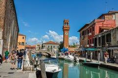Sikt av folk, byggnader och klockatornet framme av kanalen på Murano Royaltyfri Bild
