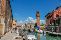 Sikt av folk, byggnader och klockatornet framme av kanalen på Murano Arkivfoton