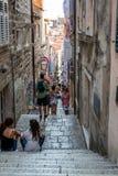 Sikt av folk på en smal gata med brant trappa i den gamla staden av Dubrovnik Kroatien royaltyfria bilder