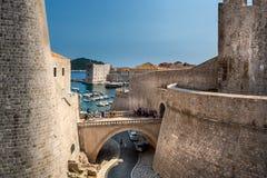 Sikt av forntida fästningstenväggar med tillfälligt folk och hamnen i bakgrunden i Dubrovnik royaltyfri bild