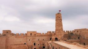 Sikt av forntida Ribat av den Monastir fästningen med tornet och flaggan av Tunisien arkivfilmer
