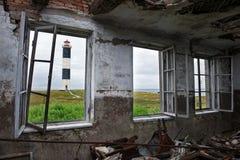 Sikt av fyren till och med fönstren av det gamla huset Arkivfoton