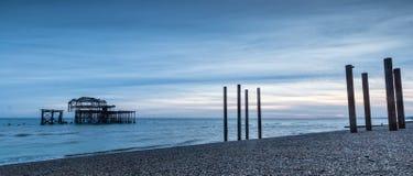 Sikt av gamla Brighton Pier som vågrullen in royaltyfri fotografi