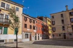 Sikt av gamla färgrika byggnader i en gränd och fyrkanten i Venedig Royaltyfri Foto