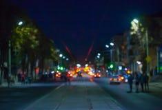 Sikt av gatan i staden på den suddiga natten, var rida bilar, spårvagnglödljus och medelbillyktor Royaltyfria Bilder
