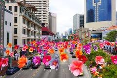 Sikt av gatan med många pappers- blommor i Singapore Arkivfoto