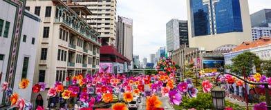 Sikt av gatan med många pappers- blommor i Singapore Arkivbild