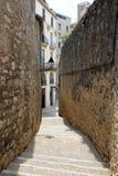 Sikt av gatan mellan de två väggarna i den judiska fjärdedelen av Girona, Spanien royaltyfri bild