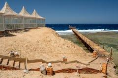 Sikt av gazeboen och banan till träpir på Calimera Habiba Beach Resort royaltyfria foton