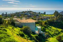 Sikt av gröna kullar och hus som förbiser Stilla havet Arkivfoto