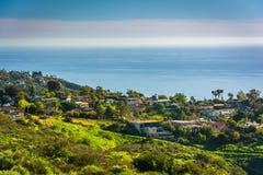 Sikt av gröna kullar och hus som förbiser Stilla havet Royaltyfria Bilder