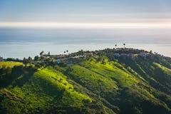 Sikt av gröna kullar och hus som förbiser Stilla havet Arkivbild