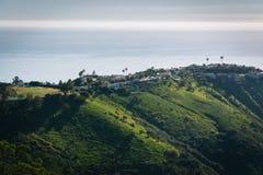 Sikt av gröna kullar och hus som förbiser Stilla havet Royaltyfria Foton