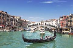 Sikt av Grand Canal, gondol med turister och den Rialto bron Venedig royaltyfri bild