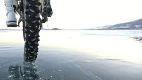 Sikt av gummihjulet Skytte 180fps Kvinnan rider cykeln på isen Is av det djupfrysta Laket Baikal Gummihjulen på lager videofilmer