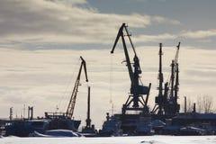 Sikt av hamnstaden på den soliga vinterdagen - last sträcker på halsen i ishamnen, kontur Royaltyfri Bild