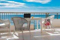 Sikt av havet från balkong med den vita tabellen och cheas, blå sk royaltyfri foto