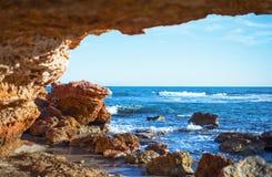 Sikt av havsvågorna och himlen från en stengrotta royaltyfri fotografi