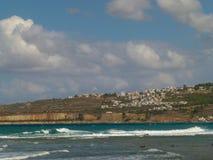 Sikt av husen av Chania till och med kanalen med turkoshavet och vita lamm, blå himmel med vita moln arkivfoto